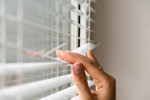 Hand on Window Blinds